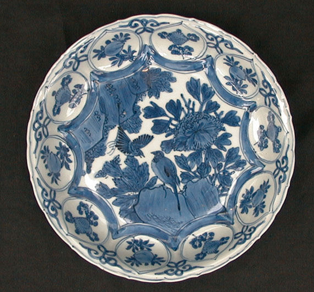 Chinese blue and white kraak dish, Wanli (1573-1619), flying birds and flowering peonies in a rocky landscape with  border roundels of peach and misc flowers.