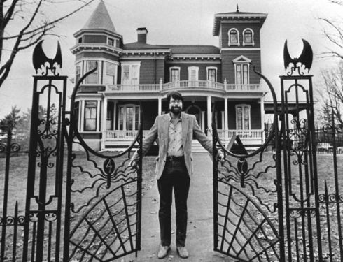 Steven King standing at the gate of his house in Bangor Maine