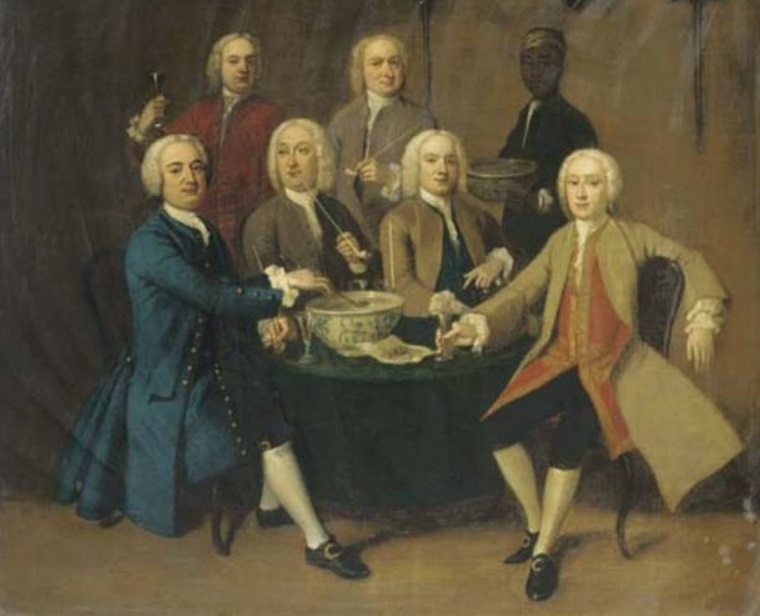Gentlemen drinking and smoking pipes round a table in an interior, a servant bearing a bowl of punch (English School)