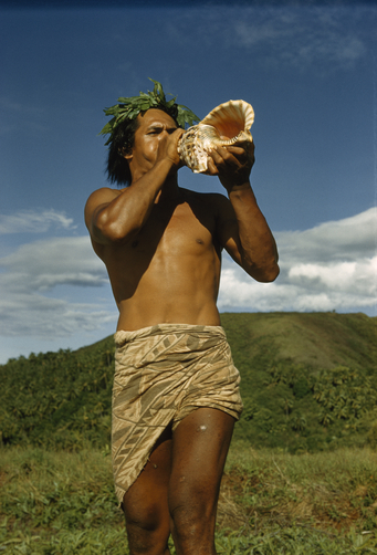 A man sounds a blast on a triton shell--which has spiritual significance in Hawaii