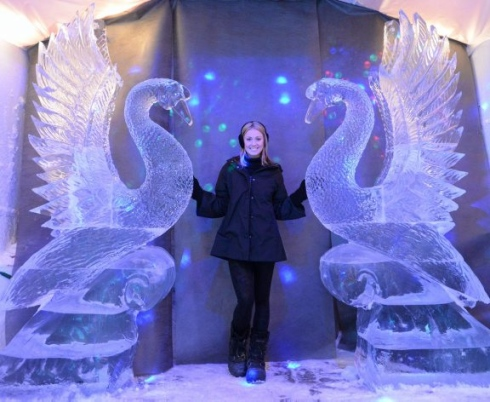 Bartender stands between two giant ice swan statues at the ice bar at Damenti's Restaurant