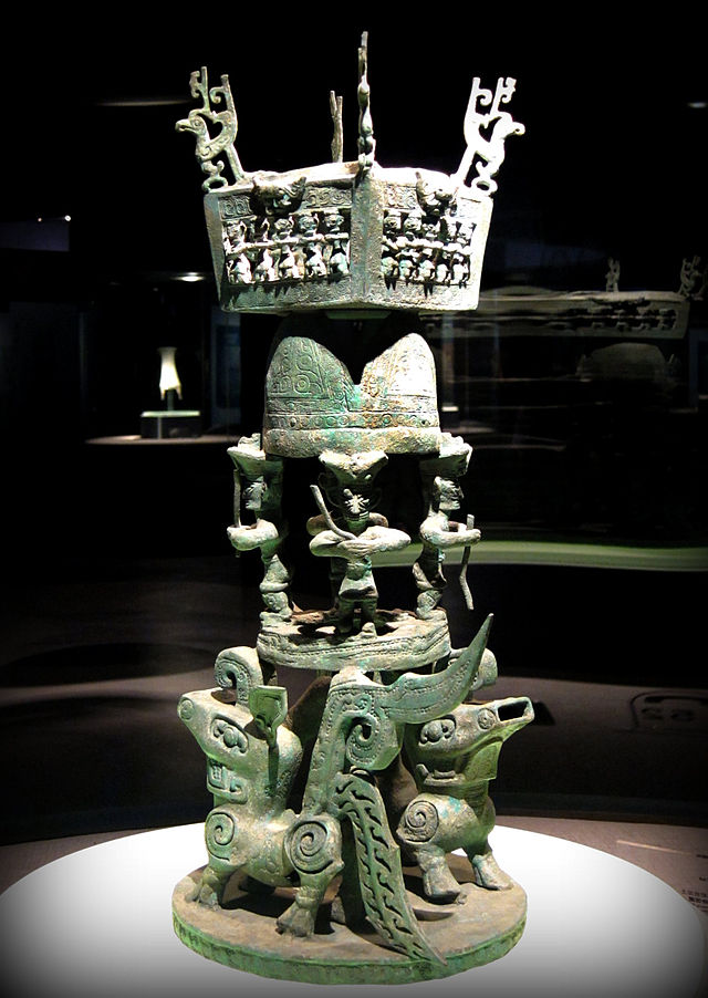 A sacrificial altar with several four-legged animals supporting bronze humanoid figures (Sanxingdui, ca. 1300-1200 BC, bronze)