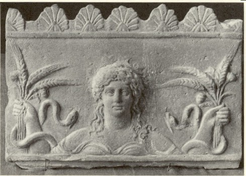 Ancient Greek stone carving of the goddess Ceres with poppies, shafts of wheat, and snakes